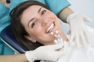 A dentist showing porcelain teeth to patient -Dental Implant Dentist in Hollywood, FL, Implant Dentistry in Hollywood FL